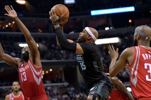 Grizzlies guard Vince Carter, center, splits the defense of the Rockets' James Harden, left, and Corey Brewer to get off a shot in the second half of Saturday night's game in Memphis, Tenn. The Rockets won 119-95.