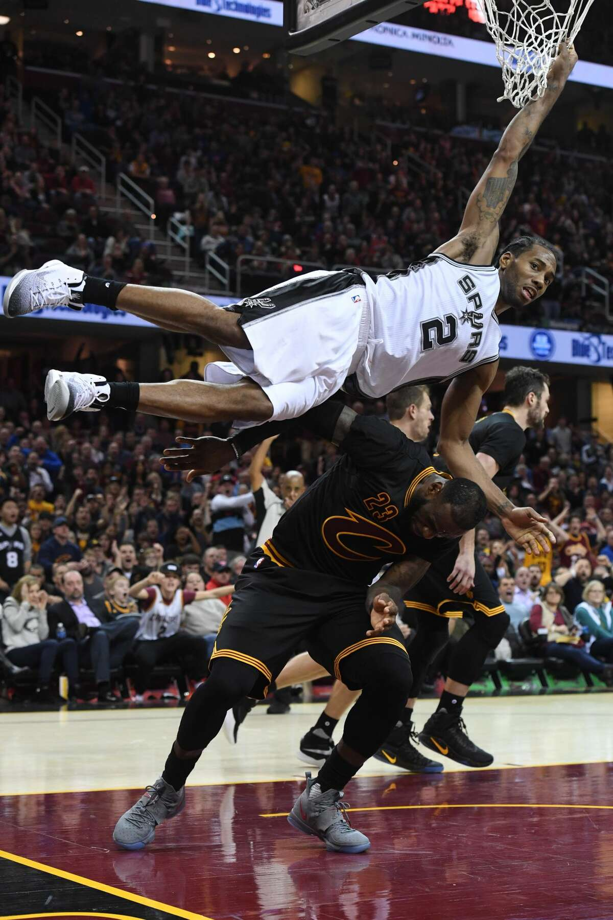CLEVELAND, OH - JANUARY 21: Kawhi Leonard #2 of the San Antonio Spurs hangs on the net to avoid landing on LeBron James #23 of the Cleveland Cavaliers during overtime at Quicken Loans Arena on January 21, 2017 in Cleveland, Ohio. The Spurs defeated the Cavaliers 118-115. NOTE TO USER: User expressly acknowledges and agrees that, by downloading and/or using this photograph, user is consenting to the terms and conditions of the Getty Images License Agreement. Mandatory copyright notice. (Photo by Jason Miller/Getty Images)