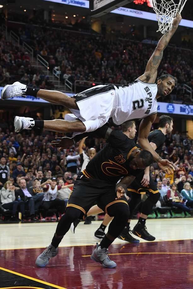 CLEVELAND, OH - JANUARY 21: Kawhi Leonard #2 of the San Antonio Spurs hangs on the net to avoid landing on LeBron James #23 of the Cleveland Cavaliers during overtime at Quicken Loans Arena on January 21, 2017 in Cleveland, Ohio. The Spurs defeated the Cavaliers 118-115. NOTE TO USER: User expressly acknowledges and agrees that, by downloading and/or using this photograph, user is consenting to the terms and conditions of the Getty Images License Agreement. Mandatory copyright notice. (Photo by Jason Miller/Getty Images) Photo: Jason Miller/Getty Images