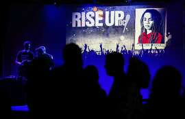"With one of Shepard Fairey's three new ""We the People"" posters in the background, dancers hit the floor at the ""Rise Up! D.C."" party in Washington, also known as the Blue Ball."