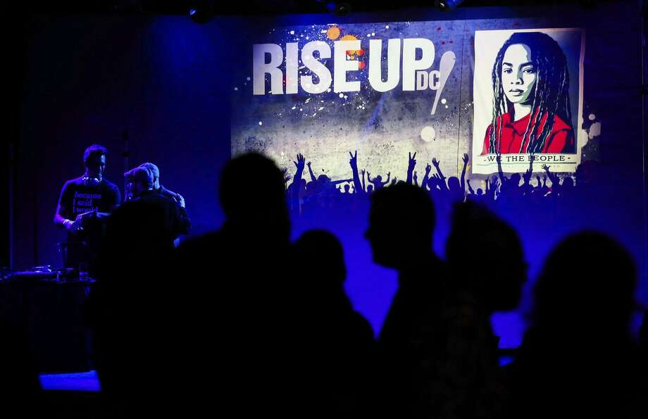 """With one of Shepard Fairey's three new """"We the People"""" posters in the background, dancers hit the floor at the """"Rise Up! D.C."""" party in Washington, also known as the Blue Ball. Photo: Gabrielle Lurie / Gabrielle Lurie / The Chronicle / ONLINE_YES"""