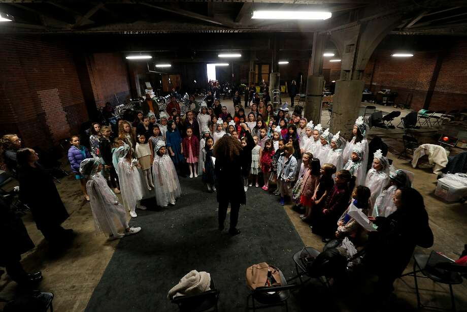 "The San Francisco Girls Chorus warms up for the opera ""Vireo"" in January at Oakland's abandoned 16th Street train station. Photo: Paul Kuroda, Special To The Chronicle"