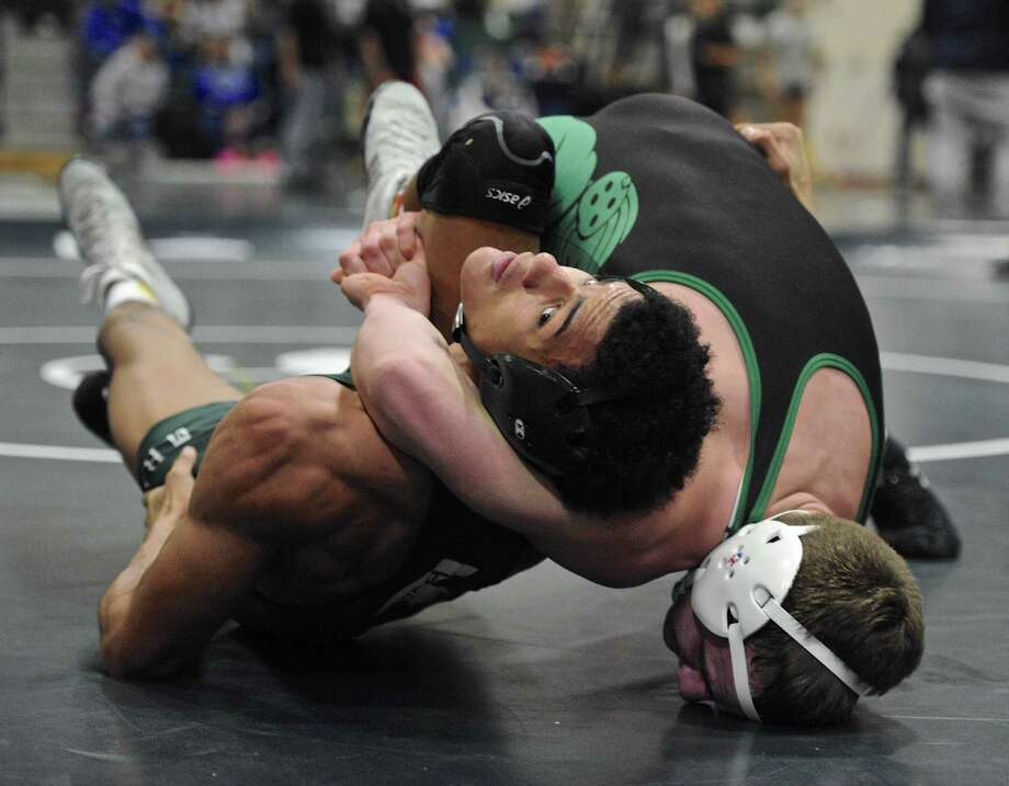 Maloney's Markeese Thompson, left, and New Milford's Cameron Berger wrestle in a 160-pound semifinal match Saturday at the New Milford tournament. Photo: H John Voorhees III / Hearst Connecticut Media / The News-Times