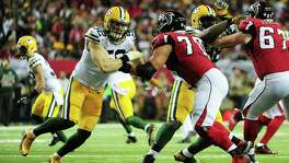 ATLANTA, GA - JANUARY 22: Clay Matthews #52 of the Green Bay Packers is blocked by Jake Matthews #70 of the Atlanta Falcons during the first quarter in the NFC Championship Game at the Georgia Dome on January 22, 2017 in Atlanta, Georgia.