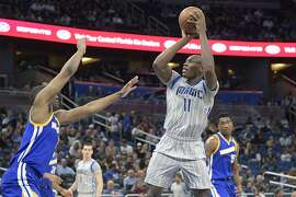 Orlando Magic center Bismack Biyombo (11) goes up for a shot between Golden State Warriors center Damian Jones (15) and forward Kevon Looney, left, during the second half of an NBA basketball game in Orlando, Fla., Sunday, Jan. 22, 2017. The Warriors won 118-98. (AP Photo/Phelan M. Ebenhack)