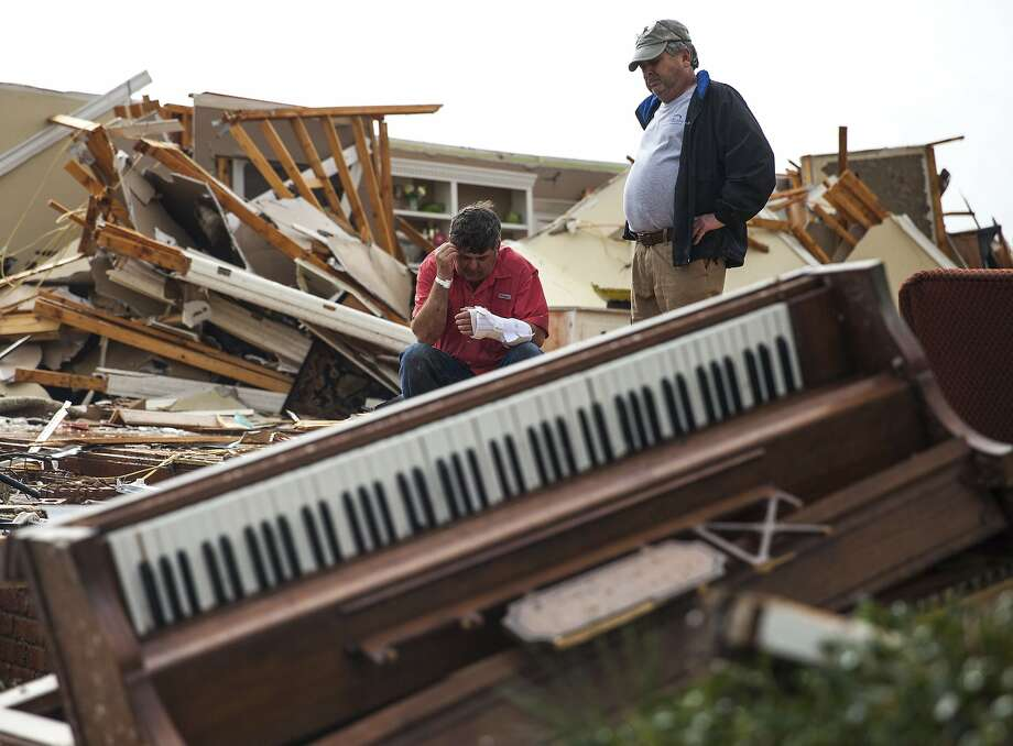 Jeff Bullard, left, sits in what used to be the foyer of his home as an unidentified man stands near, Sunday, Jan. 22, 2017, in Adel, Ga. Nathan Deal declared a state of emergency in several counties, including Cook, that have suffered deaths, injuries and severe damage from weekend storms. (AP Photo/Branden Camp) Photo: Branden Camp, Associated Press