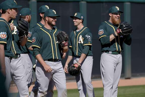 Sean Doolittle, 62 (right) and fellow pitchers share a laugh during spring training workouts for the Oakland Athletics at the Lew Wolff Training Complex in Mesa, Arizona on Thurs. February 25, 2016.