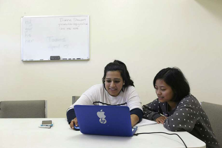 Volunteer Kiran Lalani, 20, left, helps Lun Nuam, 23, with a history assignment during and English as a Second Language class at The Center for Refugee Services, Thursday, Jan. 19, 2017. Nuam is an immigrant from Myanmar and has been in the U.S. three years. Photo: JERRY LARA, Staff / San Antonio Express-News / © 2017 San Antonio Express-News