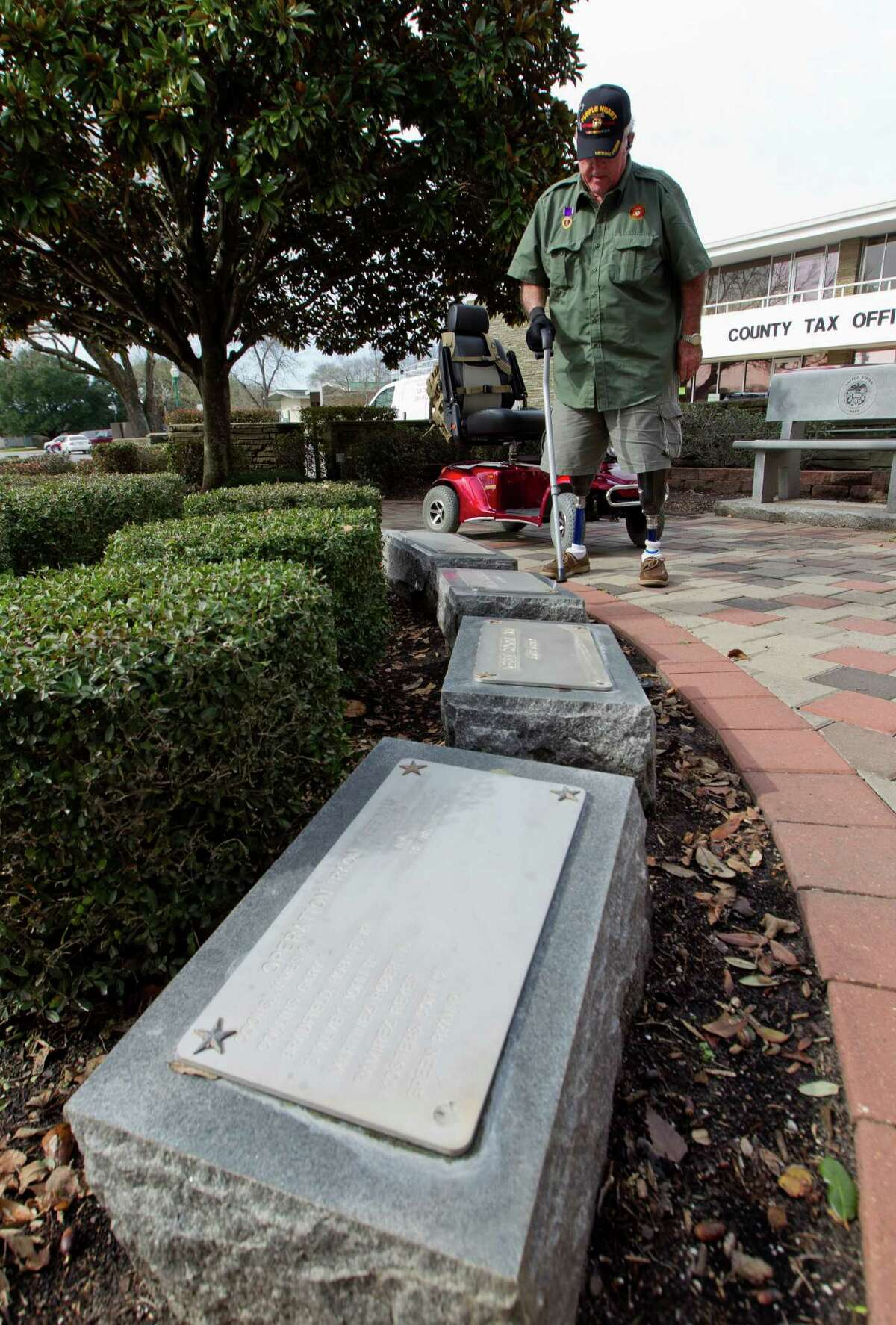 Retired United States Marine Corps Cpl. Jimmie Edwards III looks over former classmates lost serving in Vietnam during a visit to Montgomery County War Memorial Park Friday, Jan. 20, 2017, in Conroe. Edwards working to decommission the park in hopes to relocate it from its current location nestled between the county tax office and Conroe Tower to a larger, more visible and accessible location yet to be determined. The former Texas Representative and Montgomery County judge plans to meet with county leaders at Montgomery County Commissioners Court Jan. 24. Edwards lost both legs after being hit by a mortar shell while serving in Vietnam in 1969.