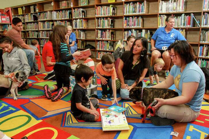 A group of children and trained therapy dogs at the  Houston Public Library, George B. Meyer, Sr. Branch. The dogs are part of a program designed to help children as they face the trials of learning to read.