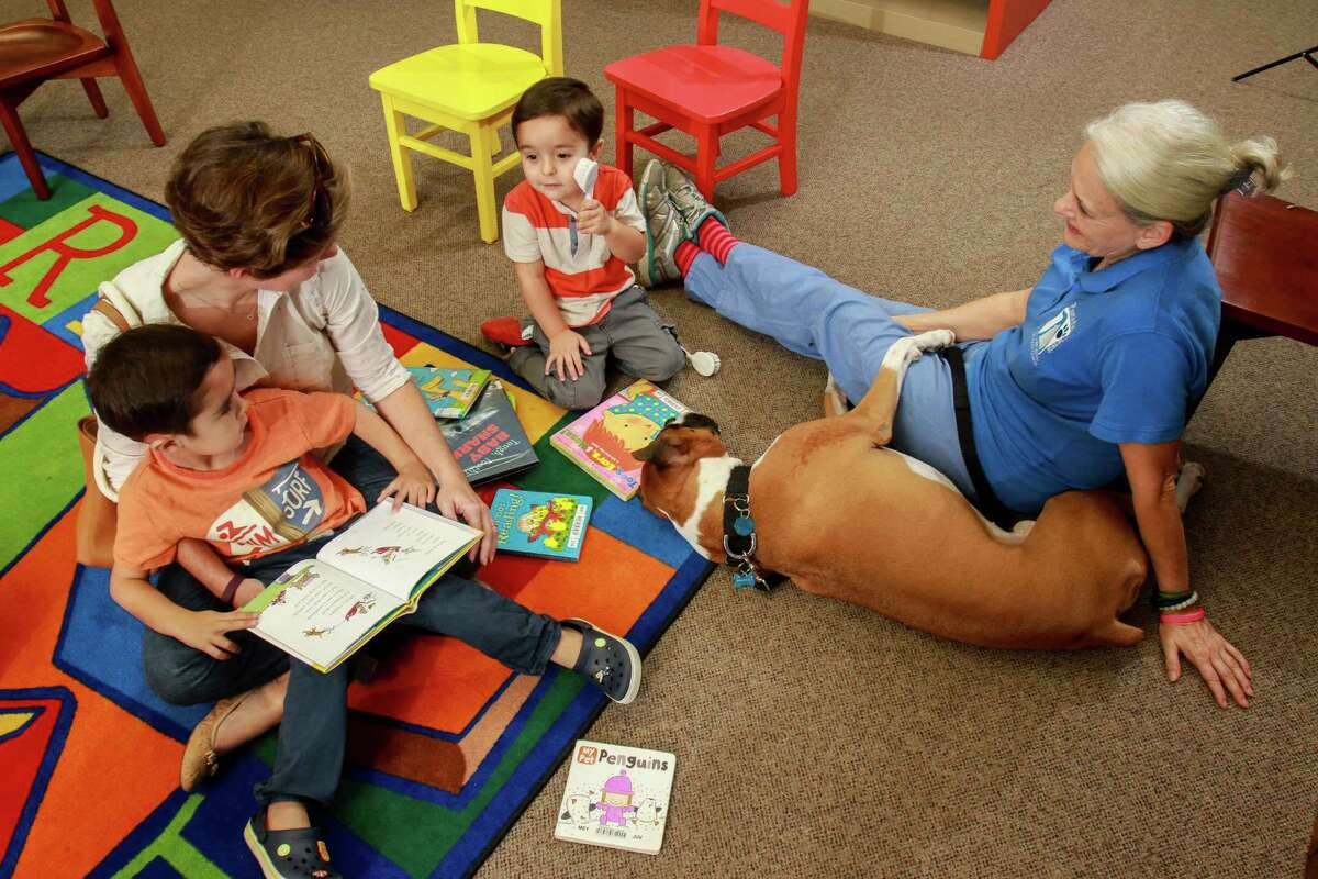 Monique Caceres reading with her sons, David, 5, left, and Ben 3, near Judith Moore and her boxer Baker, at the Houston Public Library, George B. Meyer, Sr. Branch.