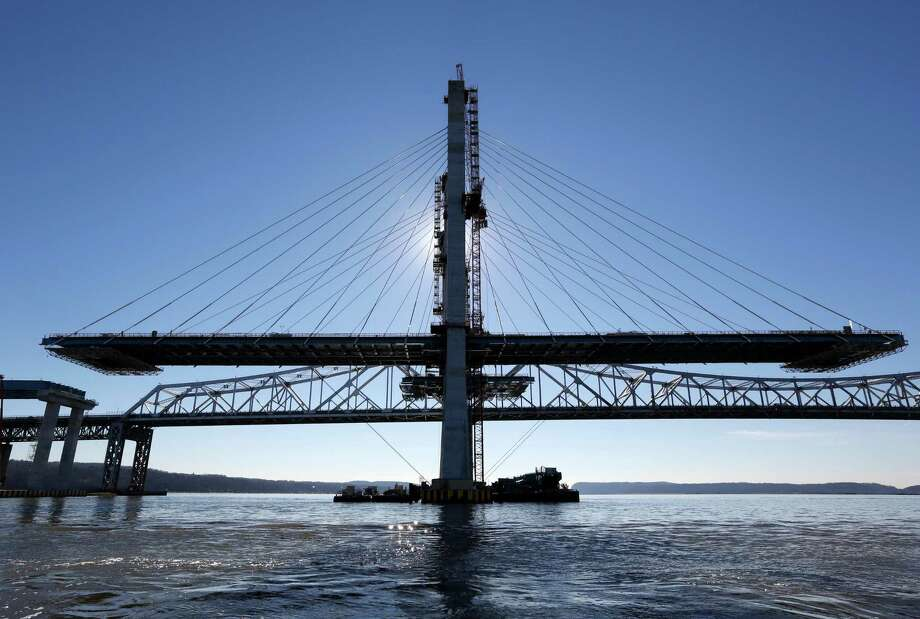A span on the new Tappan Zee Bridge, foreground, awaits completion while motorists continue to use the older bridge near Tarrytown, N.Y., Tuesday, Dec. 20, 2016. Without the bridge, the next Hudson crossing is 20 miles north and carries a sliver of the traffic volume. The next crossing to the south is through traffic-choked Manhattan, barely visible 25 miles in the distance. (AP Photo/Seth Wenig) Photo: Seth Wenig / Copyright 2016 The Associated Press. All rights reserved.