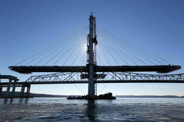 A span on the new Tappan Zee Bridge, foreground, awaits completion while motorists continue to use the older bridge near Tarrytown, N.Y., Tuesday, Dec. 20, 2016. Without the bridge, the next Hudson crossing is 20 miles north and carries a sliver of the traffic volume. The next crossing to the south is through traffic-choked Manhattan, barely visible 25 miles in the distance. (AP Photo/Seth Wenig) ORG XMIT: NYSW111