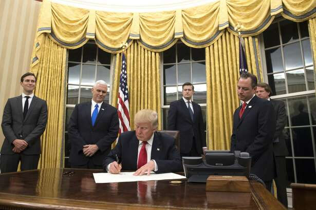 President Donald Trump prepares to sign a confirmation for Homeland Security Secretary James Kelly, in the Oval Office at the White House in Washington, D.C. on January 20, 2017.