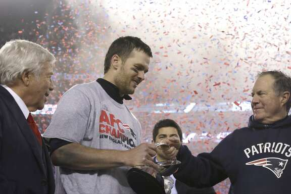 New England Patriots head coach Bill Belichick, right, passes the AFC Championship trophy to quarterback Tom Brady after winning the AFC championship NFL football game against the Pittsburgh Steelers, Sunday, Jan. 22, 2017, in Foxborough, Mass. At left is team owner Robert Kraft. The Patriots defeated the the Steelers 36-17 to advance to the Super Bowl. (AP Photo/Charles Krupa)