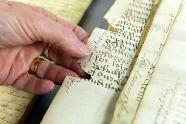 Director of Archival Services Maria Holden points out rodent damage to a parchment document from one of the  2000 boxes of Colonial-era and 18th, 19th-century New York City municipal records being preserved at the NYS Archives Wednesday January 18, 2017 in Albany, NY.  (John Carl D'Annibale / Times Union)
