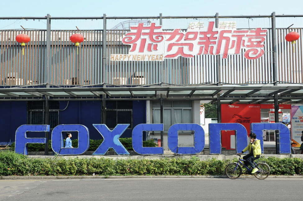This picture taken on February 22, 2013 shows people walking past a Foxconn recruitment point in Shenzhen, south China's Guangdong province. AFP PHOTOSTR/AFP/Getty Images