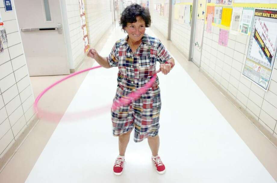"Ronne Garber, Stark Elementary School's physical education teacher and past Teacher of the Year, demonstrates her hula hooping moves in the hallway Wednesday afternoon, May 26, 2010. Garber is among the veteran teachers who have decided to take an early retirement package being offered by the Board of Ed. For some, the financial package offered incentive, for Garber the decision has been difficult. She is not ready to retire, but she is frustrated with the direction of the district and can't turn down the package. Every Wednesday she leads ""fitness finders"" which features yoga, dancing and hula hooping for third graders. Photo: Keelin Daly / Stamford Advocate"