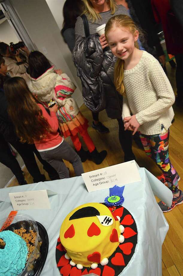 Allie Polacek, 8, of New Canaan, gets the news that the smiley-face cake she made with friend Annebel Slocum won craziest cake at New Canaan CARES 2nd annual cake-baking contest, Sunday, Jan. 22, 2017, at HALO Studios in New Canaan, Conn. Photo: Jarret Liotta / For Hearst Connecticut Media / New Canaan News Freelance