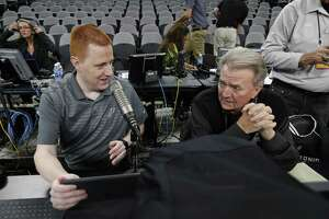Jonathan Sanford (left) chats with Spurs game statistician Bill Mochel before tipoff against the Timberwolves at the AT&T Center.