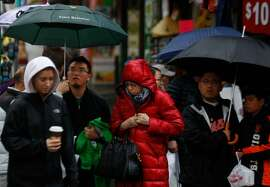 People prepare to cross the street as rain falls in Chinatown on Jan. 7, 2017 in San Francisco, Calif. Scattered showers and periodic downpours will continue on Monday around the Bay Area