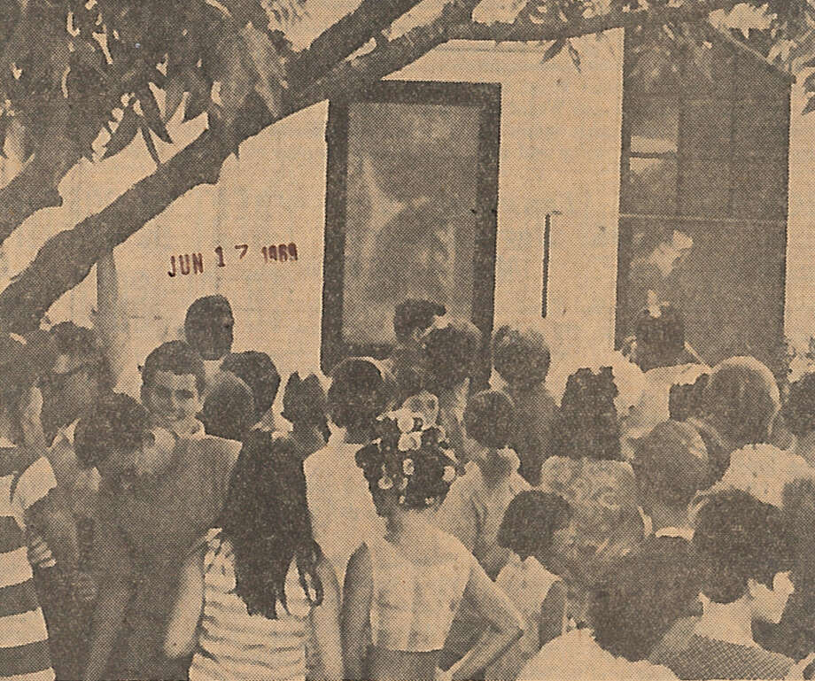 """Persons from among all age gropus press close to the back screen door Monday of the C.P. Bass home, 816 Ave. C in Port Neches, to see a likeness of the head profile of Jesus Christ. The image's chin is just above the head of a youth in the center. The hair of the likeness is long and curves downward to the left."" Enterprise staff photo by John Snell. Published June 17, 1969 The appearance of Jesus Christ's profile on a screen door at 816 Ave. C, Port Neches, in 1969, brought thousands of visitors to Mid-County. Photo: Enterprise File"