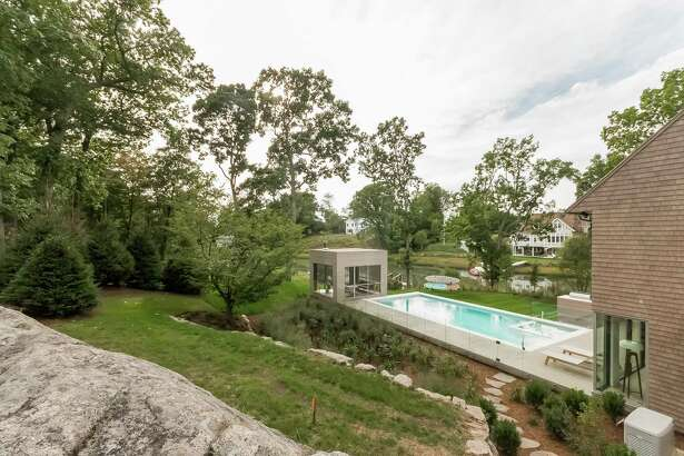 """The yard of this contemporary house at 1 Beverly Place has a patio, raised pool area, built-in gas grill and a cube that serves as an """"outdoor"""" family room. It is heated, has a fireplace and high-end speakers."""