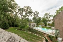 "The yard of this contemporary house at 1 Beverly Place has a patio, raised pool area, built-in gas grill and a cube that serves as an ""outdoor"" family room. It is heated, has a fireplace and high-end speakers."