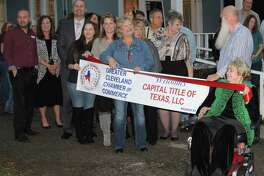 Capital Title Business Development Manager Angela DeDear prepares to cut the ribbon commemorating the business joining the Greater Cleveland Chamber of Commerce. The ribbon cutting ceremony took place at Capital Title's location on 211 S. Bonham Avenue on Jan. 19.