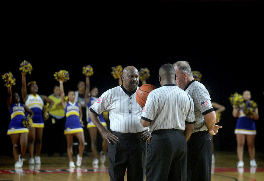 BISD chapter referees (from left) Banks Wynn, Pastor Carlton Sharp, and Phillip Pollock huddle mid-court as they await the start of the second quarter during Friday night's rivalry match-up between Central and Ozen at the Montagne Center. Photo taken Friday, January 20, 2017 Kim Brent/The Enterprise Photo: Kim Brent / Beaumont Enterprise