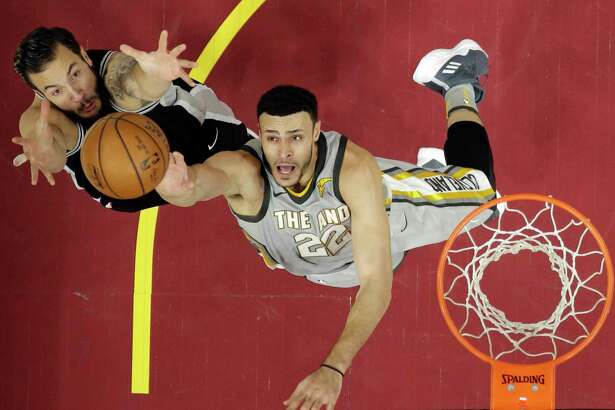 San Antonio Spurs' Dejounte Murray (5) drives past Cleveland Cavaliers' Jordan Clarkson (8) in the first half of an NBA basketball game, Sunday, Feb. 25, 2018, in Cleveland. (AP Photo/Tony Dejak)