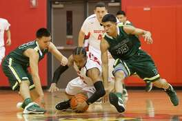 McCollum's Santiago Vasquez (left) and Roger Martinez fight for the ball with Southside's Drevon Brown on Feb. 7, 2014.