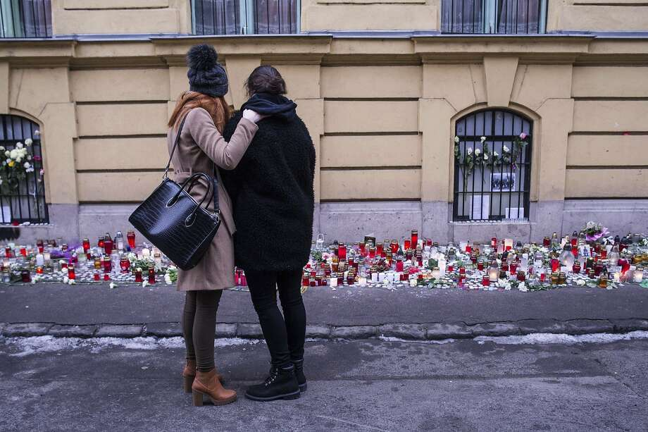 Two girls embrace at a memorial to the bus-crash victims outside their school in Budapest, Hungary. Photo: Bea Kallos, Associated Press