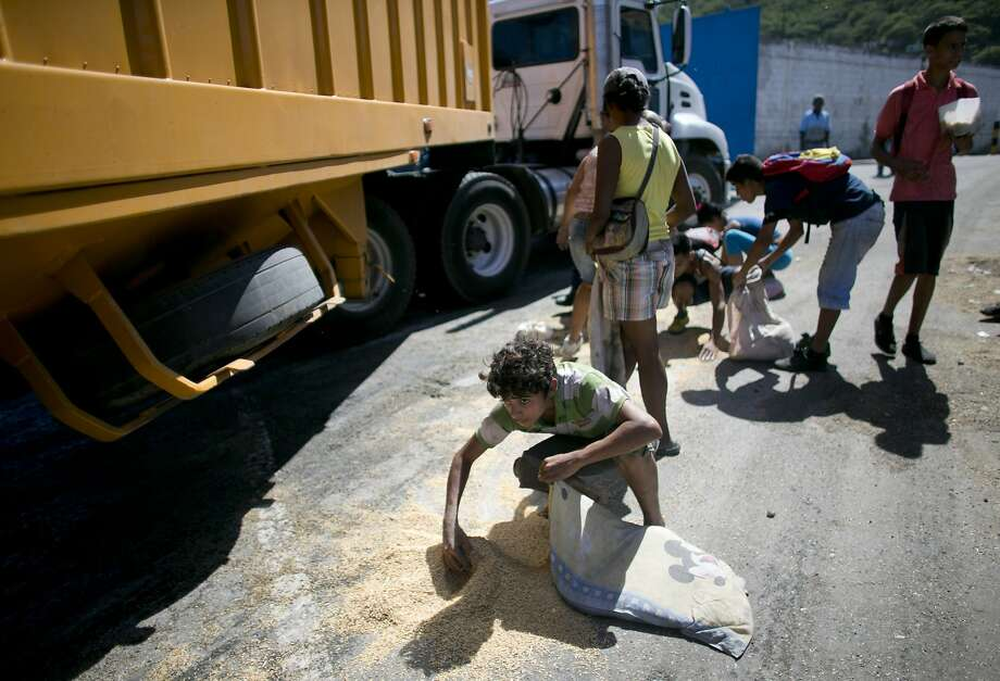 A boy uses a pillowcase to collect rice that shook loose from a cargo truck in November at the port in Puerto Cabello, Venezuela. Trafficking in hard-to-find food has become big business. Photo: Ariana Cubillos, Associated Press