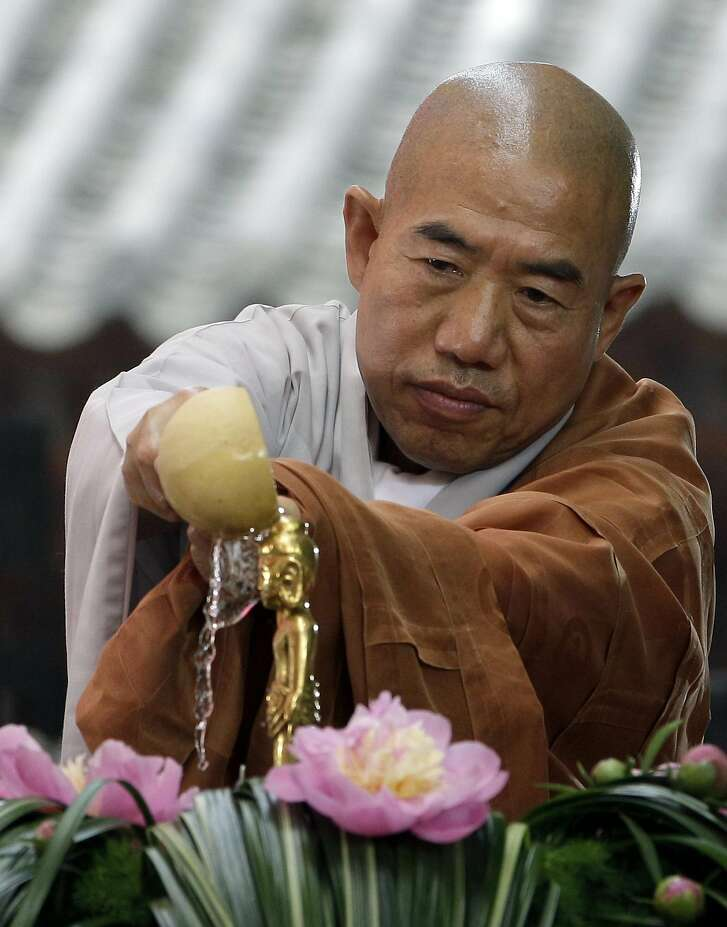 A South Korean monk pours water on a small statue of Buddha during a service to celebrate Buddha's birthday at Jogye temple in Seoul, South Korea, Monday, May 28, 2012.  (AP Photo/Lee Jin-man)