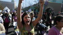 "Trinity student Olivia Garza shouts as she marches with about 1,200-1,500 people who gathered at City Hall on Saturday, Jan. 21, 2017 for San Antonio's version of the women's march happening in Washington, D.C. to oppose Donald Trump's inauguration. The march started in downtown and concluded at Estela's Mexican Restaurant on the city's Westside. Advertised as a march against ""hate, misogny, transphobia, homophobia, xenophobia,"" the organizers and protestors railed against Trump's comments against women and minorities. (Kin Man Hui/San Antonio Express-News)"