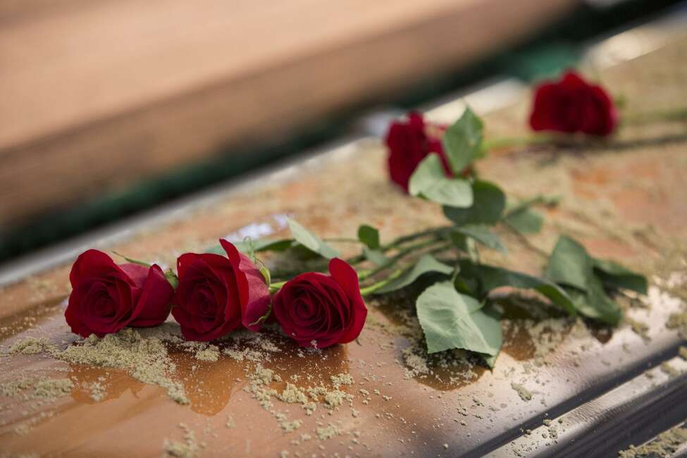Flowers lay on the casket after the graveside service for Archbishop Emeritus Patrick Flores at the San Fernando Cemetery in San Antonio, Texas on January 17, 2017.