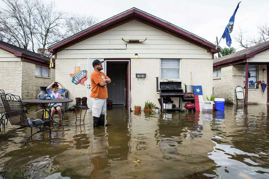 Carlos Gutierrez is calf-deep in water from heavy overnight rains at his house  near the 2600 block of Creston on Wednesday. Photo: Brett Coomer, Staff / © 2017 Houston Chronicle