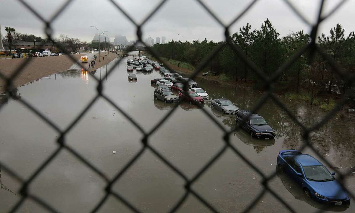 Abandoned cars on 288 near Calumet stuck in flooding from the bayou after heavy nightfall rain on Wednesday, Jan. 18, 2017, in Houston. ( Elizabeth Conley / Houston Chronicle )