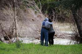 Family and friends embrace at the edge of Alameda Creek as Alameda County rescue personnel search Alameda Creek, in Fremont, Ca., on Monday Jan. 23, 2017, for a missing 18-year-old woman whose car plunged into the swollen creek saturday morning.
