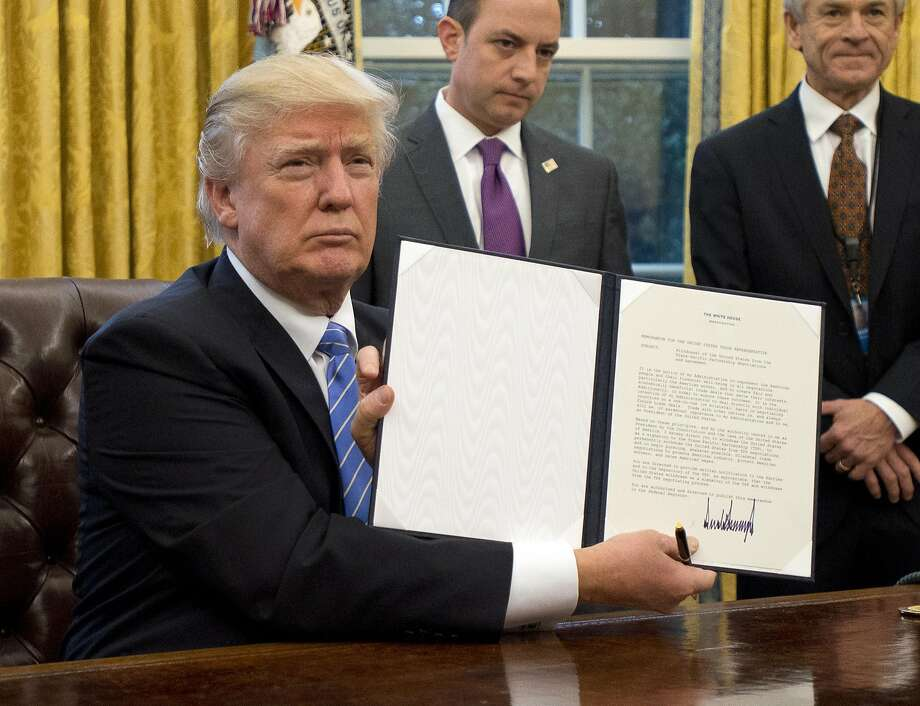 """WASHINGTON, DC - JANUARY 23:  (AFP OUT) U.S. President Donald Trump shows the Executive Order withdrawing the US from the Trans-Pacific Partnership (TPP) after signing it in the Oval Office of the White House in Washington, DC on Monday, January 23, 2017.  The other two Executive Orders concerned a US Government hiring freeze for all departments but the military, and """"Mexico City"""" which bans federal funding of abortions overseas. (Photo by Ron Sachs - Pool/Getty Images) *** BESTPIX *** Photo: Pool"""