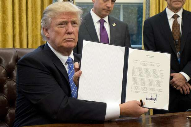 """WASHINGTON, DC - JANUARY 23:  (AFP OUT) U.S. President Donald Trump shows the Executive Order withdrawing the US from the Trans-Pacific Partnership (TPP) after signing it in the Oval Office of the White House in Washington, DC on Monday, January 23, 2017.  The other two Executive Orders concerned a US Government hiring freeze for all departments but the military, and """"Mexico City"""" which bans federal funding of abortions overseas. (Photo by Ron Sachs - Pool/Getty Images) *** BESTPIX ***"""