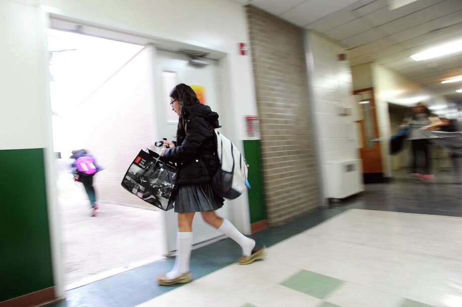 A student leaves Trinity Catholic Middle School to catch the bus in Stamford, Conn. on Monday, Jan. 23, 2017. Photo: Michael Cummo / Hearst Connecticut Media / Stamford Advocate