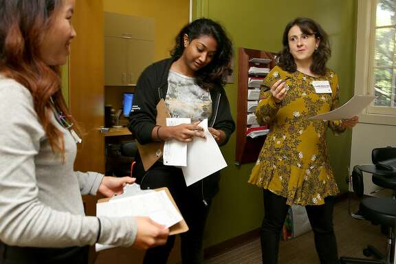 Volunteer health workers Julia Quon (left),  Camille Dickenson (right) and workforce coordinator Sindura Reddy (middle) get ready for a pre-shift huddle before clients arrive at the Women's Community Clinic on Monday, January 23, 2017, in San Francisco, Calif.    Women on the San Francisco board of supervisors will pass a resolution pledging to uphold universal sexual health care and reproductive planning in San Francisco.