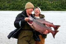 Retired couple fishing in Alaska. The seniors are holding large salmon and wearing cold weather gear. Heads thrown back laughing with pure joy.