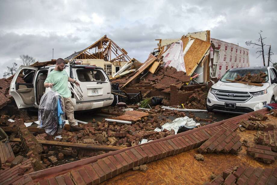 A man who gave only his first name, Ren, gets clothing from a car parked at a home that was smashed by a tornado in Adel, Ga. Photo: Branden Camp / Associated Press / Branden Camp / Associated Press / FR171034 AP