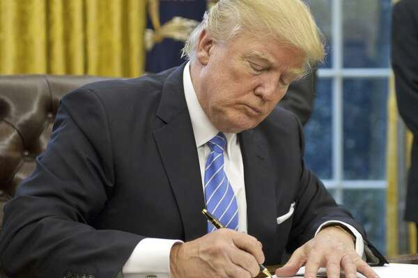 President Trump signs executive orders on trade and government hiring at the White House.