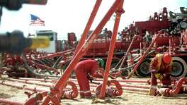 Halliburton employees work on high-pressure pipes supplying a hydraulic fracturing site managed by Octane Energy near Stanton in West Texas.