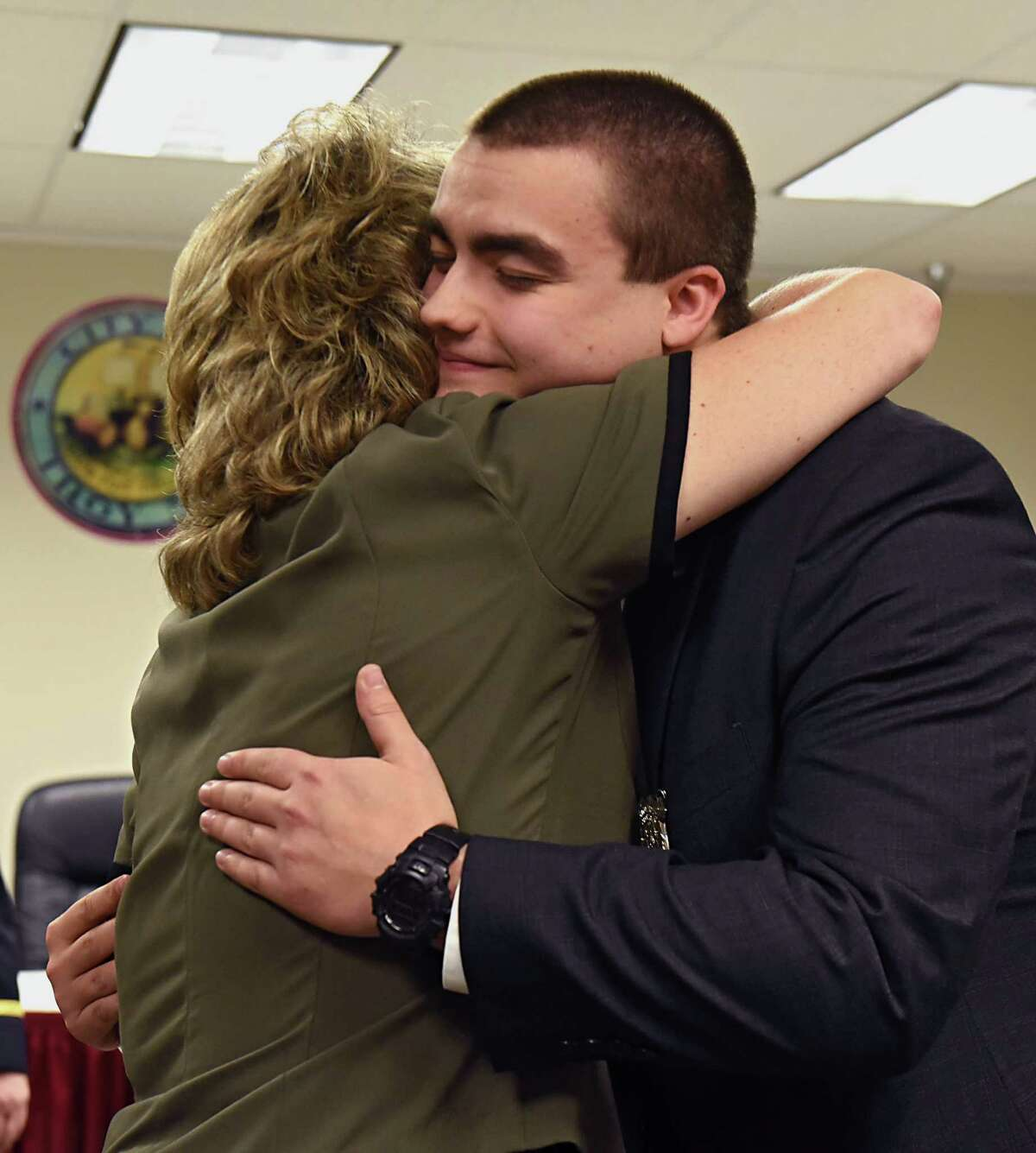 New police officer Corey Otterbeck, 22, gets a hug from his mother, Julie, after she pinned his new badge on him at a swearing-in ceremony for seven new police officers on Monday, Jan. 23, 2017 in Troy, N.Y. Otterbeck was a Troy Police Cadet from 2011-2015. (Lori Van Buren / Times Union)