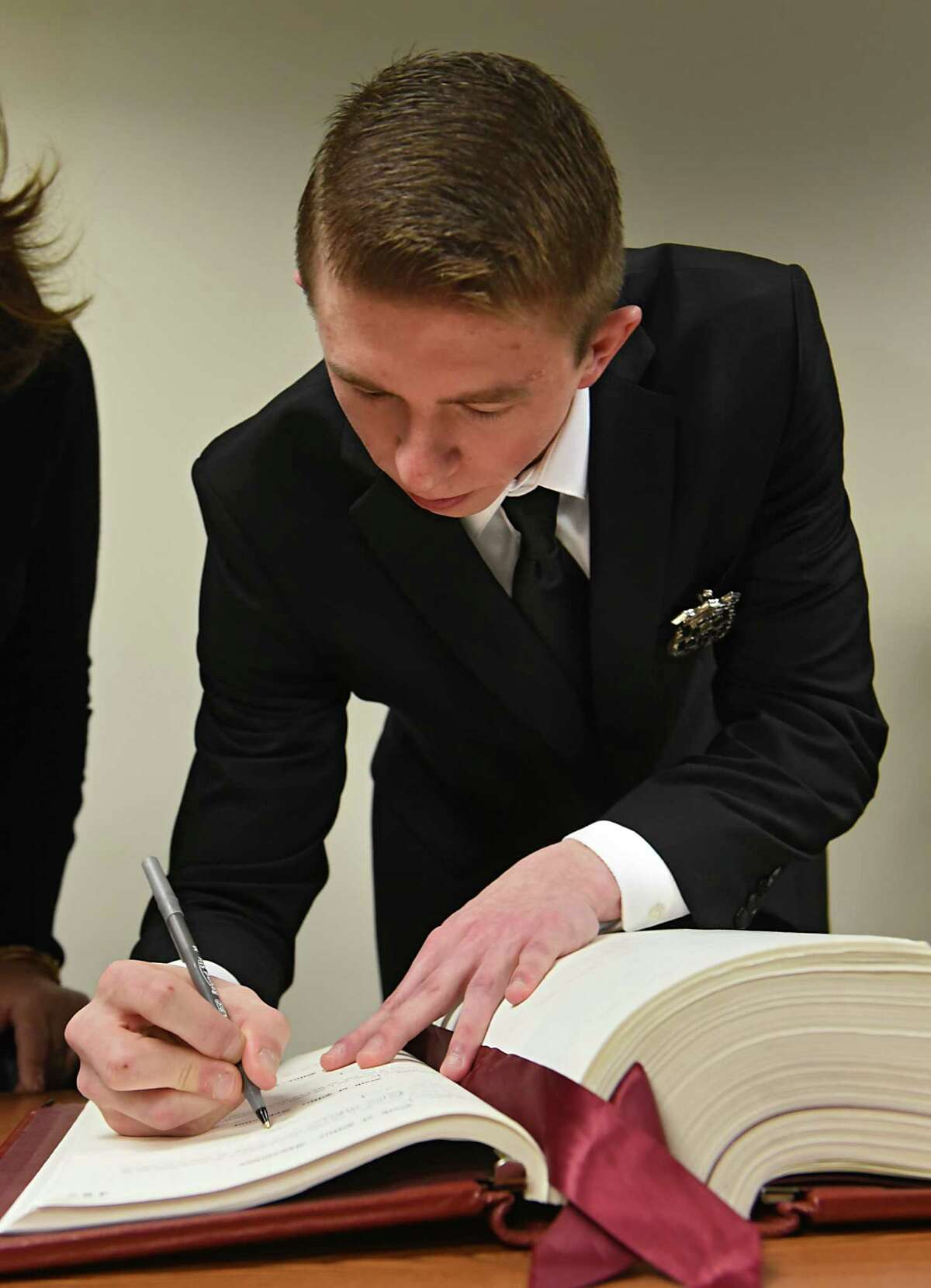 Adam Harbour, 22, signs an official book at a swearing-in ceremony for seven new police officers on Monday, Jan. 23, 2017 in Troy, N.Y. Harbour was a Troy Police Cadet. (Lori Van Buren / Times Union)